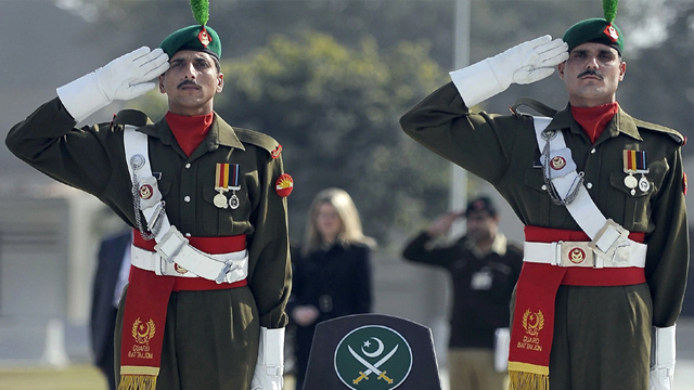 Pakistan Army personnel saluting in British-style, palms facing outward.